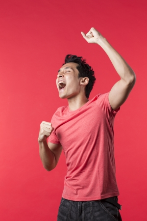 excited: Cheerful Asian man celebrating with his arm up. In front of Red background. Stock Photo