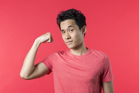 Portrait of Asian man standing flexing his bicep against red background. photo