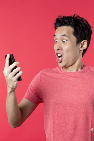 Angry Asian man talking on cell phone. Standing against red background. Stock Photo
