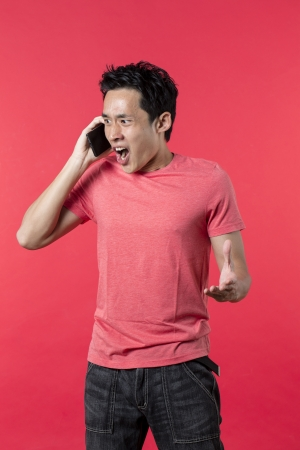 Angry Asian man talking on cell phone. Standing against red background. photo