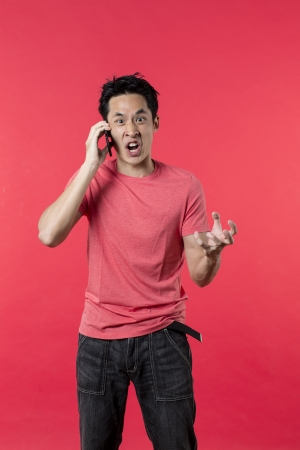 bad feeling: Angry Asian man talking on cell phone. Standing against red background. Stock Photo