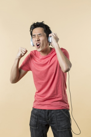 Handsome Asian man wearing earphones singing and dancing to music. standing against cream background. photo