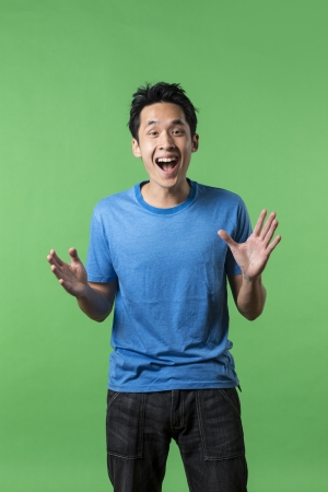 Amazed: Surprised and amazed looking Asian man standing against green background. Stock Photo