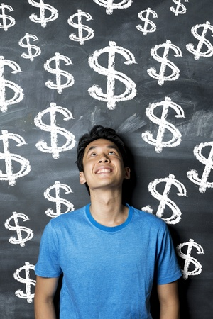 Happy Asian man standing in front of lots of dollar sign written on a chalkboard. photo