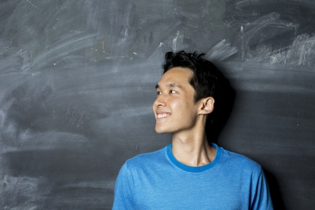 excited: Closeup portrait of a happy AsianChinese man looking to left. Standing next to a blackboard. Stock Photo
