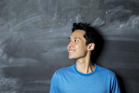 vzrušený: Detailním portrét šťastný asijské  čínské muž hledá doleva. Stojící vedle tabuli.