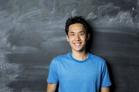 Portrait of a happy AsianChinese man standing next to a blackboard.