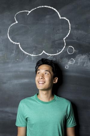 pensamiento creativo: Hombre asi�tico feliz que se coloca debajo de la burbuja del pensamiento dibujado a mano en una pizarra oscura.