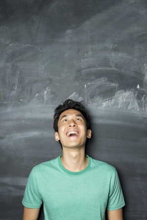 Closeup portrait of a happy AsianChinese man looking above. Standing next to a blackboard. photo