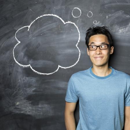 estudiantes universitarios: Hombre asiático feliz que se coloca al lado de lado el pensamiento de burbuja dibujado en una pizarra oscuro. Foto de archivo