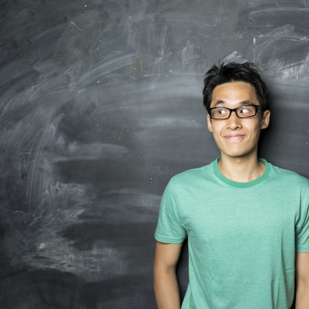 sideways: Closeup portrait of a happy AsianChinese man looking to left. Standing next to a blackboard. Stock Photo