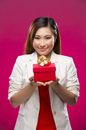 Happy Asian woman holding a christmas gift. Smiling happy girl on deep pink background. photo