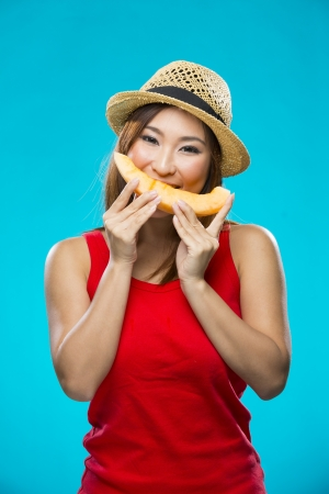 Happy Asian Woman holding a slice of melon fruit on colorful background. Healthy eating concept. Young and fresh Asian female model on blue background. photo