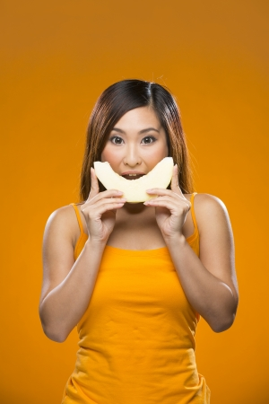 biting: Happy Asian Woman holding melon on colorful background. Healthy eating concept. Young and fresh Asian female model on orange background. Stock Photo