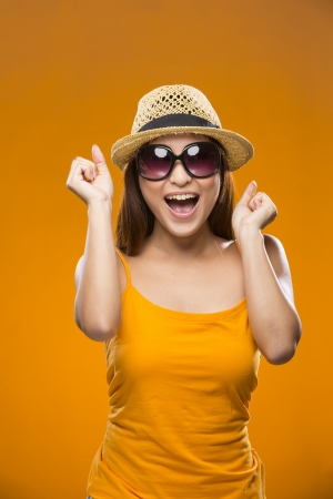 Portrait of surprised Asian Woman. Young fresh Chinese female model on bright orange background.  photo