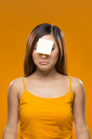 forgetful: Portrait of a forgetful Asian Woman with a yellow sticky note on her forehead. Young fresh Chinese female model on bright orange background.   Stock Photo