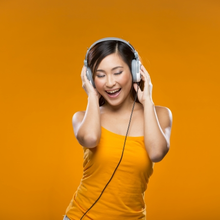 Happy Chinese Woman listening to music on headphones. Young fresh Asian female model on orange background. photo