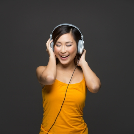 Happy Chinese Woman listening to music on headphones. Young fresh Asian female model on grey background. photo
