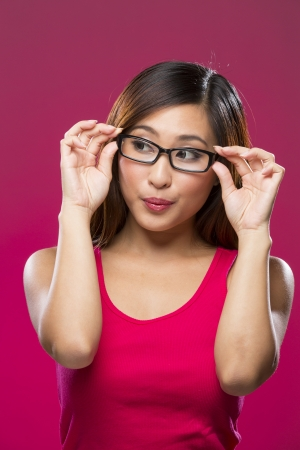 Portrait of Asian Woman looking away. Young fresh Chinese female model on bright pink background.  photo