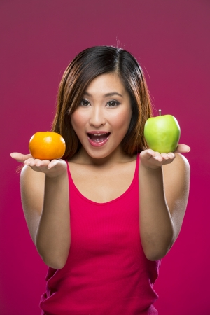 Happy Asian Woman holding fruit on colorful background. Healthy eating concept. Young and fresh Asian female model on a dark pink background. photo