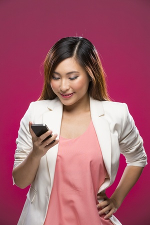 Stylish Chinese Woman using a smart phone. Young and fresh Asian female model a bright pink background. Stock Photo - 22179645