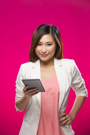 Stylish Chinese Woman using a digital tablet PC. Young and fresh Asian female model a bright pink background. photo