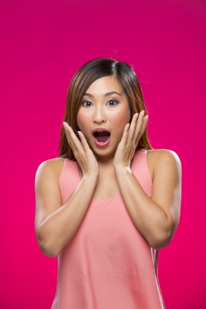 asian woman face: Portrait of surprised Asian Woman. Young fresh Chinese female model on bright orange background.  Stock Photo