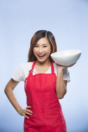 Happy Asian Woman wearing a red apron and holding a mixing bowl. Young and fresh Asian female model on blue background.  photo