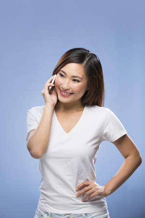 Stylish Chinese Woman using a smart phone. Young and fresh Asian female model a bright blue background. photo