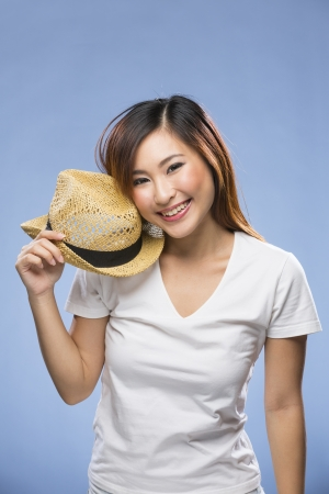 Fashionable Asian Woman wearing straw hat. Young fresh Chinese female model on blue background.  photo