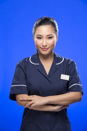 Young Asian Female Nurse holding a stethoscope. Young and fresh Asian female model on blue background.  Stock Photo