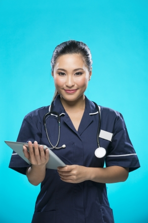 Chinese Female nurse holding a digital tablet & wearing a green scrubs plus stethoscope. Asian female model on blue background. photo