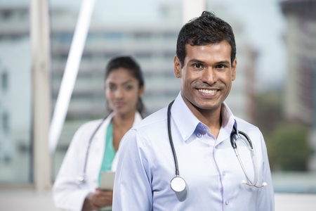 Portrait of a male Indian doctor standing in front of his colleague with a stethoscope around his neck  photo