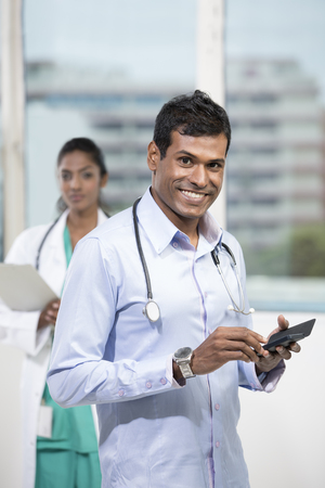 Portrait of a happy male Indian doctor using a smart phone photo