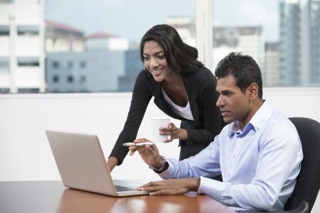 Hombre de negocios indio y una mujer trabajando juntos en un escritorio en una oficina photo
