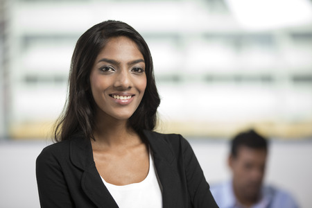 Portrait of an Indian female office executive standing in an office. photo