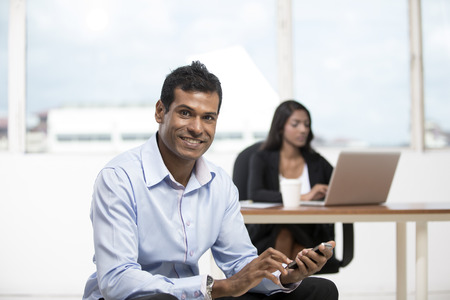 Portrait of an Indian business man using a smartphone photo