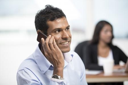 Portrait d'un homme d'affaires indien en utilisant un smartphone