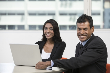 indian businessman: Indian business man and woman working on a laptop while having a meeting.