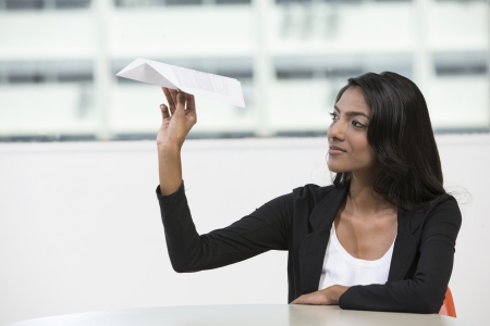 thoughtful woman: Thoughtful female Indian office worker playing with paper airplance