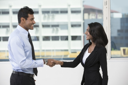 Indian business man and woman shaking hands in the office. Cheerful Asian colleagues or client greeting each other. photo