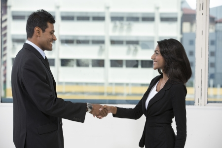 Indian business man and woman shaking hands in the office. Cheerful Asian colleagues or client greeting each other. Stock Photo