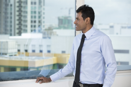 man looking out: Thoughtful Indian business man looking out of an office window. Stock Photo