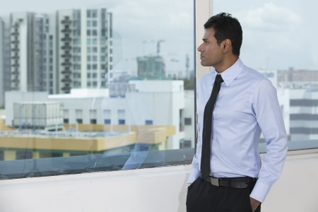 Thoughtful Indian business man looking out of an office window. photo
