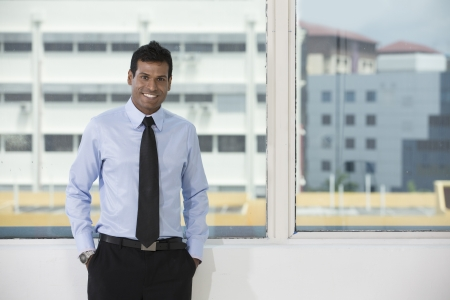 Indian business man standing next to office window taking a break photo