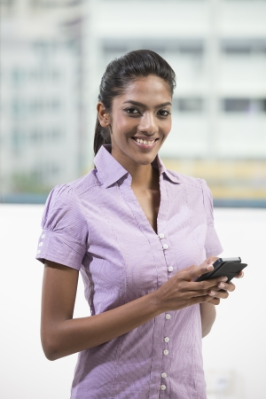 south asian: Young female Indian office executive using a smart phone