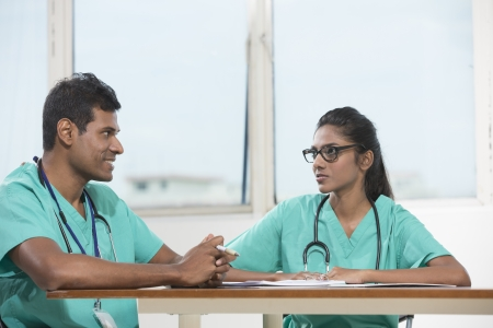Two Indian doctors sitting working at a desk together Stock Photo - 22240237