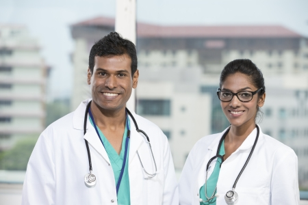 Portrait of two Indian doctors standing with a stethoscopes around there necks  photo