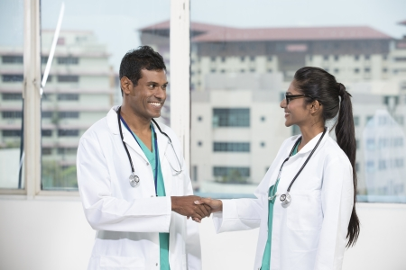 Portrait of Two happy Indian doctors shaking hands photo