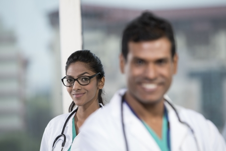 Portrait of a female Indian doctor standing with her colleague photo